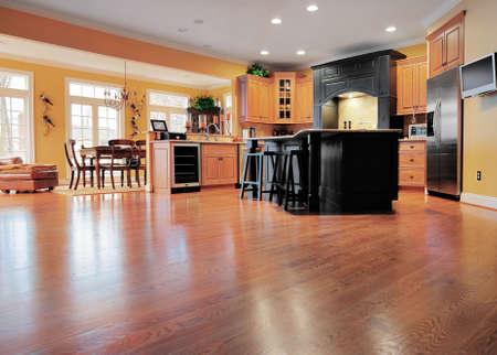 iluminados: Casa interior muestra una gran extensión de tarimas de madera en primer plano, una cocina y comedor en el fondo. Formato horizontal.
