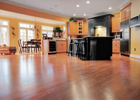 Home interior shows a large expanse of wood flooring in the foreground and a kitchen and dining room in the background. Horizontal format. Stock Photo