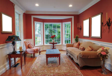 View of a traditional living room with a bay window in the background. Horizontal format.