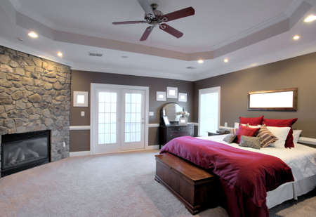 fan ceiling: Interior of a large modern bedroom with a fireplace and ceiling fan. Horizontal format.