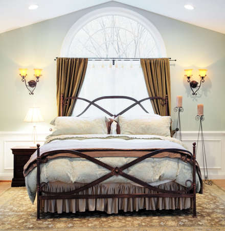 Interior of an upscale bedroom with arched window, vaulted ceiling, and ornate metal bed frame. Square format.