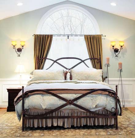 arcuate: Interno di una camera da letto di lusso con finestra ad arco, con soffitto a volta, ornato e da soffitto cornice del letto di metallo. Formato quadrato.