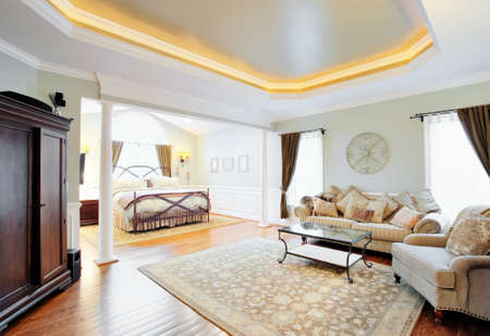 window curtains: View of a sitting area and bed in a master suite with coved ceiling. Horizontal format. Stock Photo