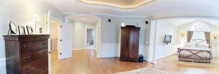 Panoramic view of a master suite interior, containing a bed and dressers. Horizontal format.