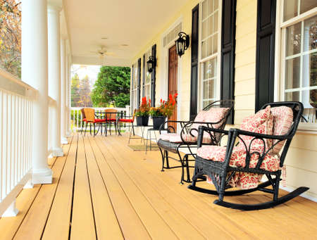 front porch: Low angle view of a large front porch with furniture and potted plants. Vertical format.
