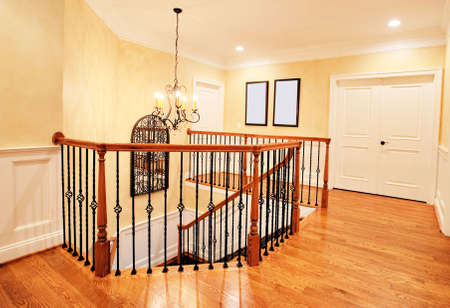 banister: Interior of an upscale home, showing the upper hallway and top of the staircase. Horizontal format. Stock Photo