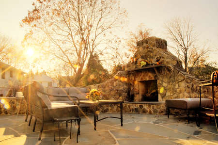 stone fireplace: Low-angle view of a flagstone patio with an outdoor stone fireplace and furniture. Rays of sunlight stream down. Horizontal format.