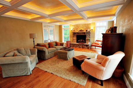 footstool: View of an upscale living room interior with a box beam ceiling. Horizontal format. Stock Photo