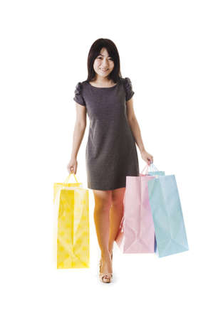 Beautiful Chinese woman with shopping bags in front of a white background. Stock Photo - 11261401