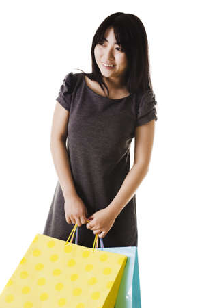 Beautiful Chinese woman with shopping bags in front of a white background. Stock Photo - 11261430