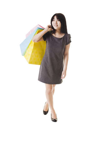 Beautiful Chinese woman with shopping bags in front of a white background.