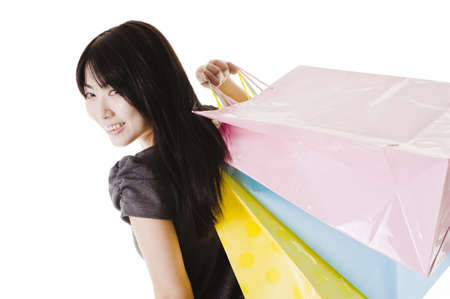 Beautiful Chinese woman with shopping bags in front of a white background. Stock Photo - 11261426
