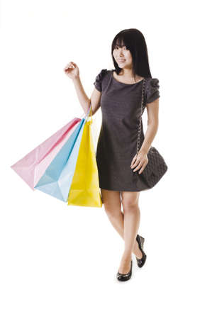 Beautiful Chinese woman with shopping bags in front of a white background. photo