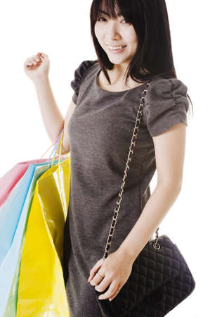 Beautiful Chinese woman with shopping bags and purse in front of a white background. photo