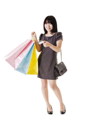 Beautiful Chinese woman with shopping bags and credit card in front of a white background.