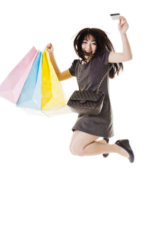 Chinese woman with shopping bags, purse, and credit card jumping into the air.