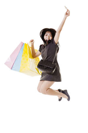 Chinese woman with shopping bags, purse, and credit card jumping into the air. Stock Photo - 11261370