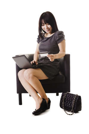 netbook: Chinese woman shopping online with a credit card. Stock Photo