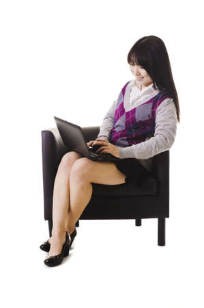 east asian ethnicity: Chinese student working on a laptop and sitting in a chair. Stock Photo