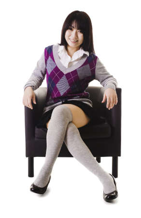 east asian ethnicity: Chinese student in a school uniform sitting in a leather chair.