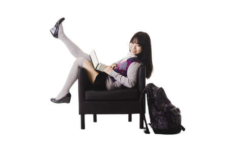 long socks: Chinese student in a school uniform sitting in a leather chair.