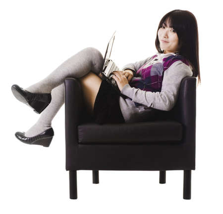 bookbag: Chinese student working on a laptop while sitting in a leather chair. Stock Photo
