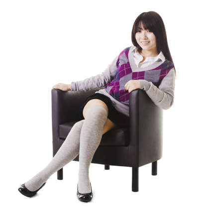 Portrait of a stylish Chinese school girl sitting in a leather chair. photo