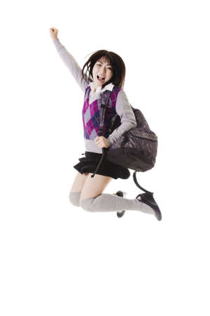 Female Chinese student with a backpack on a white background jumping in the air. photo