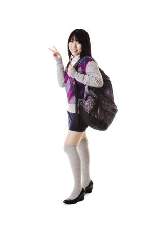 Female Chinese student with a backpack on a white background showing the peace sign. photo