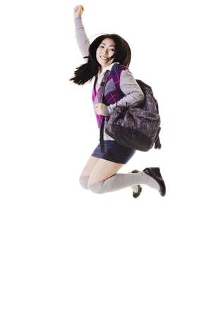 salto largo: Estudiante de chino con una mochila sobre un fondo blanco saltando en el aire.