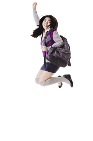 east asian ethnicity: Female Chinese student with a backpack on a white background jumping into the air.