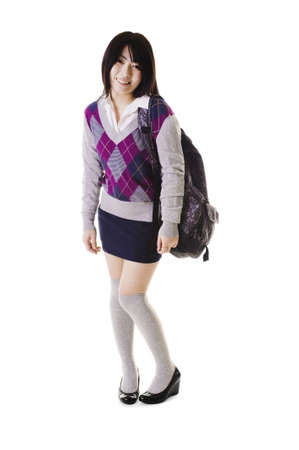 long socks: Coy female Chinese student with a backpack on a white background. Stock Photo