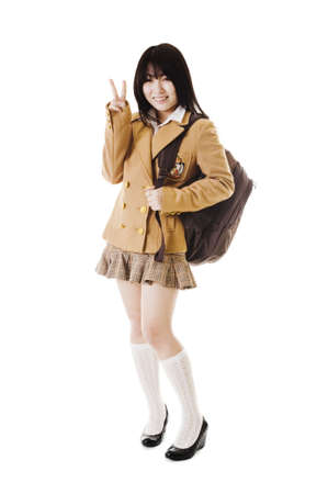 school uniform girl: Female Chinese student wearing a backpack on a white background showing a peace sign. Stock Photo