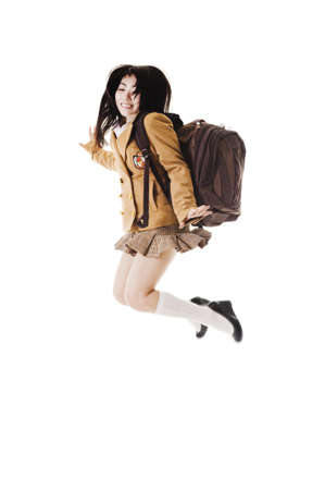 Female Chinese student wearing a backpack on a white background jumping into the air. photo