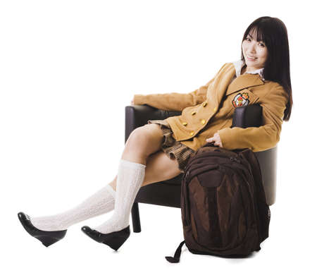 Female chinese student in a school uniform sitting in a leather chair with her bookbag. photo