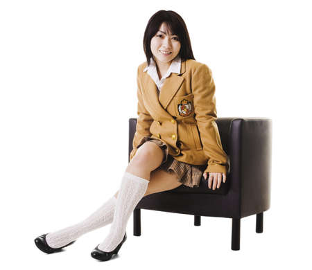 east asian ethnicity: Female chinese student in a school uniform sitting in a leather chair.