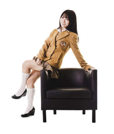 east asian ethnicity: Female chinese student in a school uniform sitting on a leather chairs arm rest.