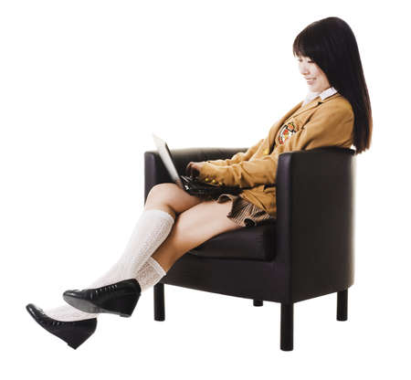 white socks: Female Chinese student reclines in a leather chair while working on a laptop.