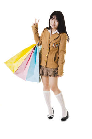 Chinese school girl wearing a uniform holds shopping bags while showing a peace sign. photo