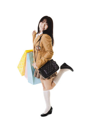Fashionable Chinese school girl wears a shoulder bag style purse and holds shopping bags.
