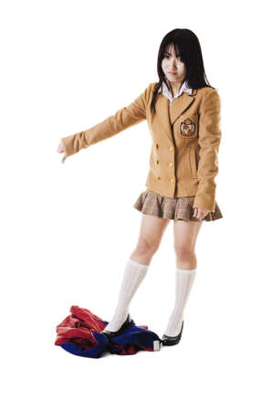 east asian ethnicity: Fashionable Chinese school girl wearing a Japanese style school uniform disapproves of an ugly looking Chinese uniform.