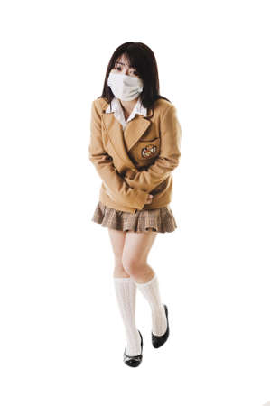 Sick Chinese school girl wearing a face mask holds her stomach in pain.