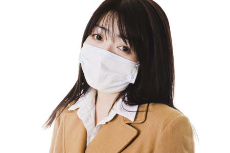 east asian ethnicity: Closeup of a sick Chinese school girl wearing a face mask. Stock Photo