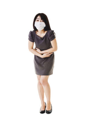 Sick fashionable Chinese woman wearing a face mask holds her stomach. photo