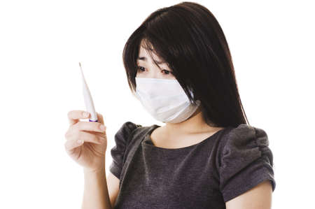 Closeup of a sick Chinese woman wearing a face mask and reading a digital thermometer. photo