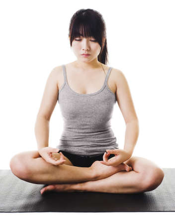 east asian ethnicity: Chinese woman sits cross legged on a yoga mat meditating. Stock Photo