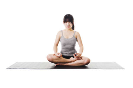 dhyana: Chinese woman sits cross legged on a yoga mat meditating. Stock Photo