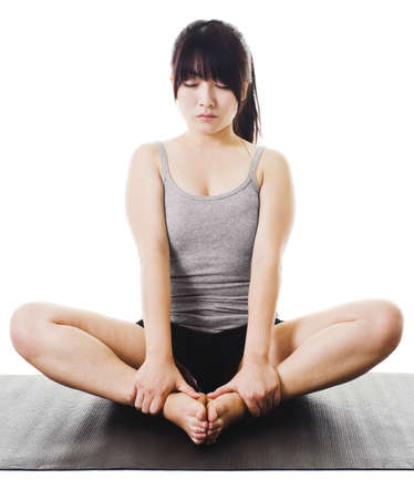 baddha: Chinese woman sitting on a yoga mat in the bound angle pose.