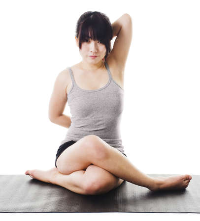 Chinese woman sitting on a yoga mat doing the cow face pose. photo