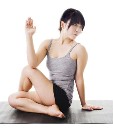 Chinese woman sitting on a yoga mat doing the half lord of the fishes pose. photo